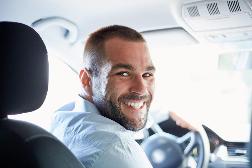 Fornøyd mann i firmabil